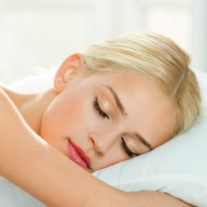 Blonde Frau schläft auf weißem Kissen
